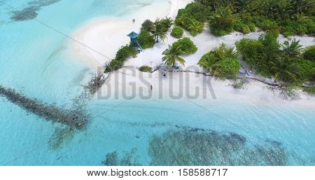 Panoramic landscape seascape aerial view over a Maldives Male Atoll island. White sandy beach with lifeguard tower seen from above.