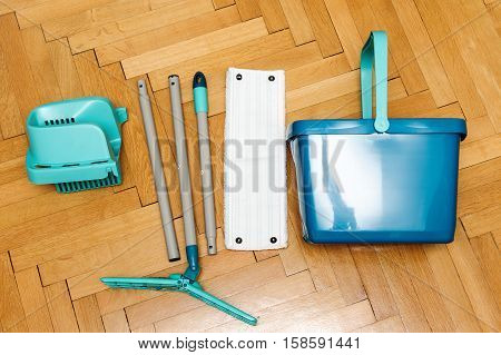 Complete sete of mop with bucket on a parquet floor - view from above - the perfect gift to make the house clean and proper