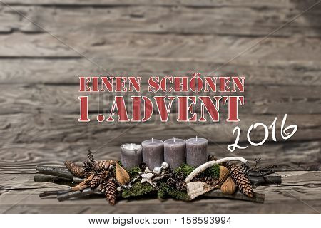 Merry Christmas decoration advent 2016 with burning grey candle Blurred background text message german 1st