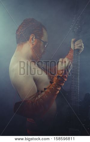 Rock star with electric guitar and concert hall smoke environment