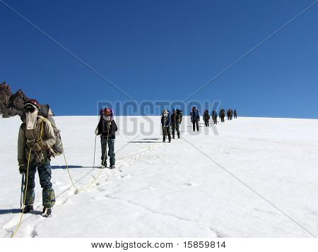 Climbers with rope on a snow glacier