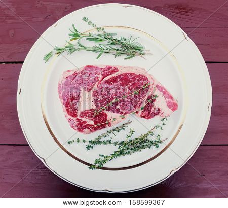 Raw rib-eye steak withe herbs on plate, old wooden table, toned image