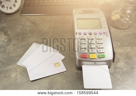Credit Card Terminal Or Edc On Cashier Table In The Store With Calculator, Clock,coins In The Bottle