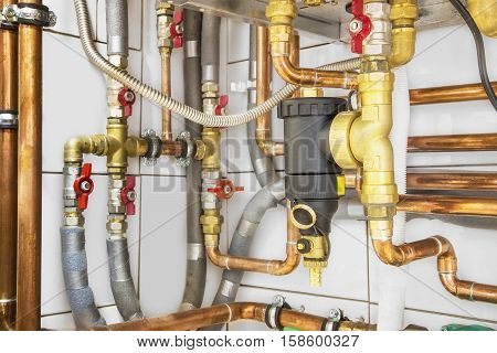 Heating system's copper pipes with ball valves on a white wall.