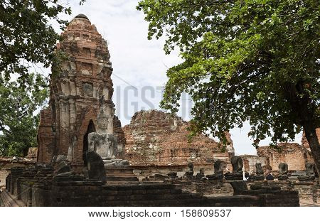 AYUTTHAYA, THAILAND - November 4, 2016: View of a meditating buddha statue sat on a platform in a ruined vihara (hall of worship) at Wat Mahathat Temple of the Great Relic a Buddhist temple in Ayutthaya central Thailand