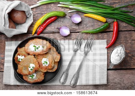 Pan with tasty potato pancakes for Hanukkah and some ingredients on wooden table
