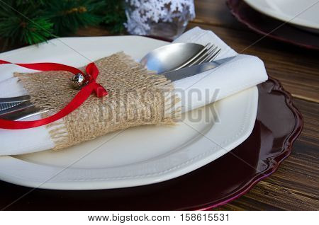 Beautiful decoration for festive dinner. Christmas table settings. White napkin with jingle bell and cutlery on wooden background.