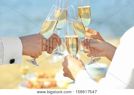 People clinking glasses at party outdoors, close up view