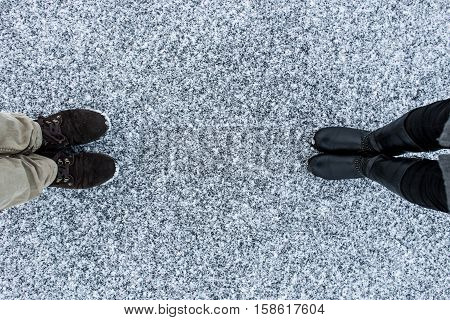 Men's and Women's boots on rough snow background. Gritty snowy covered asphalt surface. Text place. Top view