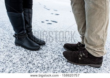 Male and Female casual boots standing on asphalt covered gritty snowY surface. Rough snowy surface. Textplace. Cold Winter. Side view.