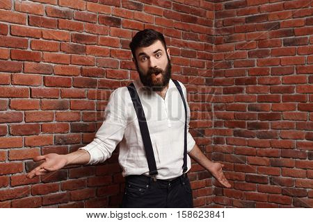 Young handsome man in suit with suspenders gesturing smoking cigar over brick background. Copy space.