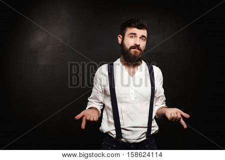 Young handsome man in suit with suspenders posing over black background. Copy space.