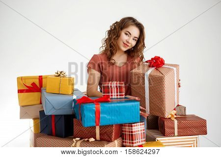 Young beautiful curly girl among gift boxes over white background Copy space