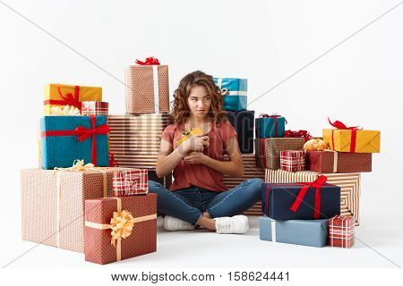 Young beautiful curly girl sitting on floor among gift boxes Isolated Copy space