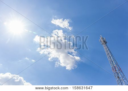 Top of telecommunication tower with clouds and the sun in the sky.