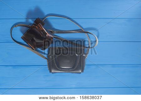 Old Photo Camera and Filmstrip on Blue Wooden Background