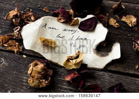 letter with emotions on a dark background with dry roses. St. Valentine's Day.