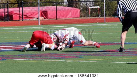 Two lacrosse players fight for the ball during a face off on game day.