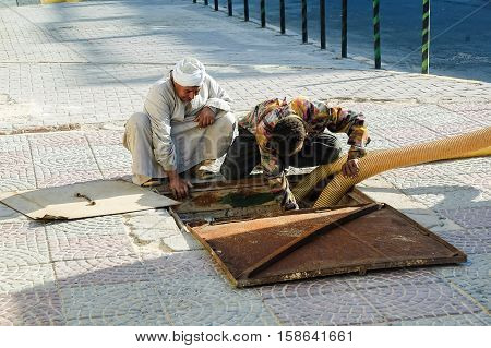 Hurghada, Egypt - November 6, 2006: Man pumping sewage from the hole - clean up sewerage overflows, cleaning pipelines and potential pollution issues