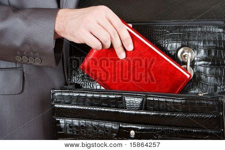 Hand Taking Red Organizer From Briefcase