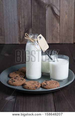 bottle of milk with carton label tag with two transparent glass, black straw and few brown cookies in gray plate on dark wooden background