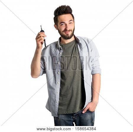 Young handsome man holding car key on grey background