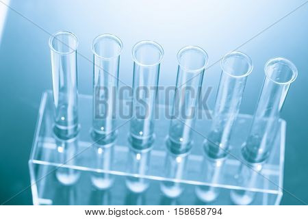 Science laboratory with  biological material samples  on a desk. Selective focus with bokeh. Rack with samples and chemicals on the background. Blue toned image. Toned image