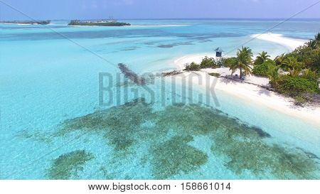 Panoramic landscape seascape aerial view over a Maldives Male Atoll island. Empty white sandy beach with lifeguard tower seen from above