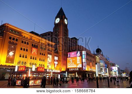 BEIJING - FEBRUARY 23, 2016: Clock tower on the shopping Wangfujing street in center of Beijing. Wangfujing one of the most famous shopping street in Beijing, is very popular among tourists and locals