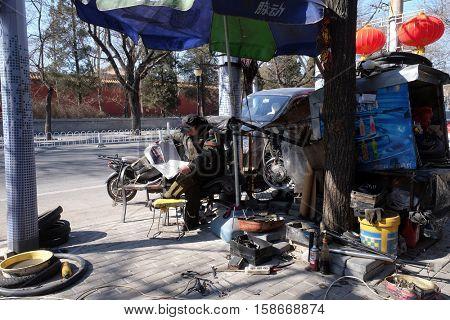 BEIJING - FEBRUARY 24: Mechanic at workshop on street in Beijing, China, February 24, 2016.