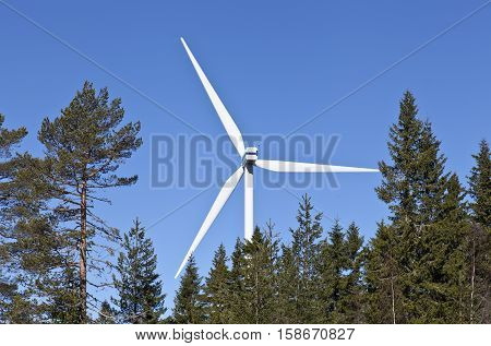 RURAL COUNTY, SWEDEN ON APRIL 21. View of a modern windmill, power plant on April 21, 2013 in Rural County, Sweden. Trees this side, blue sky. Editorial use.