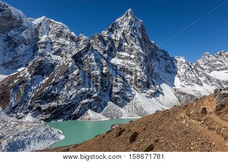 Mountain Trail On The Foreground Of A Beautiful Himalayan Landscape With Snowy Peak And Bright Blue
