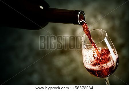 Red wine is being poured into the glass shot against dark background