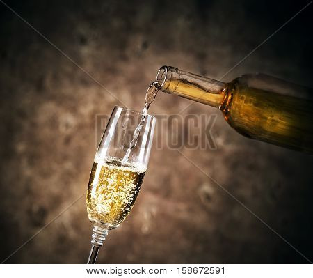 White wine pouring into a glass on dark background