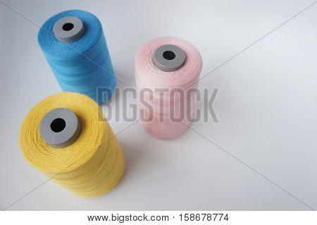 3 thread bobbins blue pink and yellow medium close up