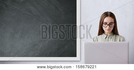 Pretty schoolgirl with long dark hair wearing glasses working with her big white laptop in the classroom. A spacious classroom with big blackboard and working student in it.