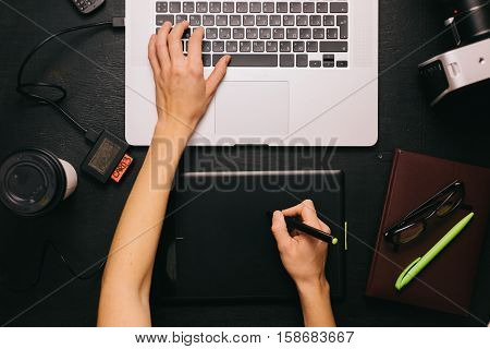 From above shot of crop hands working on laptop with graphic tablet.