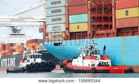 Oakland CA - October 11 2016: Tugboats VETERAN and VALOR assisting cargo ship GUNVOR MAERSK to maneuver into the Port of Oakland the fifth busiest port in the United States.