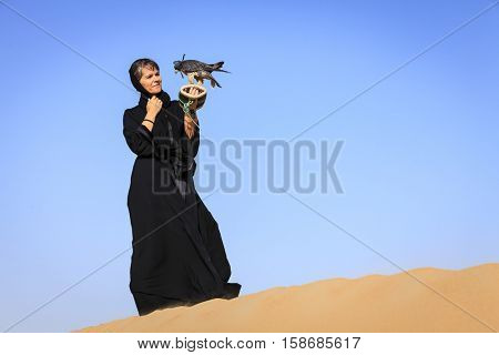 A woman in abaya with Peregrine Falcon in Dubai Desert Conservation Reserve