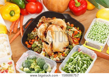 Frozen vegetables in plastic containers fried chicken in pan. Healthy freezer food and meals.