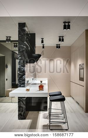 Kitchen island in a modern style with a black marble wall with a kitchen hood and a white tabletop with a stove and a sink. There are wooden lockers with oven, stools and mirror. Vertical.