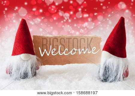 Christmas Greeting Card With Two Red Gnomes. Sparkling Bokeh And Christmassy Background With Snow. English Text Welcome