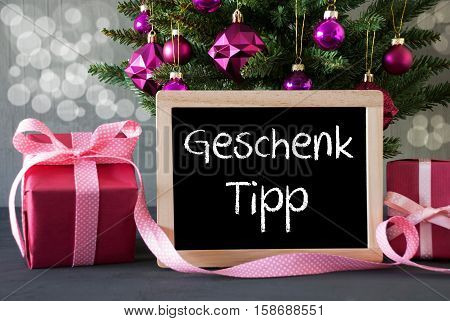 Chalkboard With German Text Geschenk Tipp Means Gift Tip. Christmas Tree With Rose Quartz Balls And Bokeh Effect. Gifts Or Presents In The Front Of Cement Background.