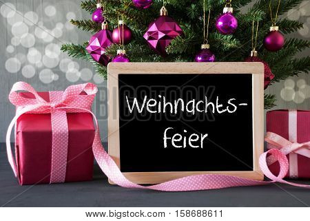 Chalkboard With German Text Weihnachtsfeier Means Christmas Party. Christmas Tree With Rose Quartz Balls And Bokeh Effect. Gifts Or Presents In The Front Of Cement Background.