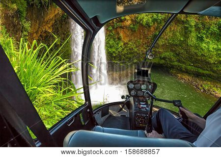 Helicopter cockpit flies in ropical Manawaiopuna Falls also called Jurassic Park Falls, Kauai, Hawaii, United States, with pilot arm and control board inside the cabin.