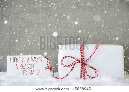 One Christmas Gift Or Present On Snow. Cement Wall As Background With Snowflakes. Modern And Urban Style. Card For Seasons Greetings. Label With English Quote Ther Is Always A Reason To Smile