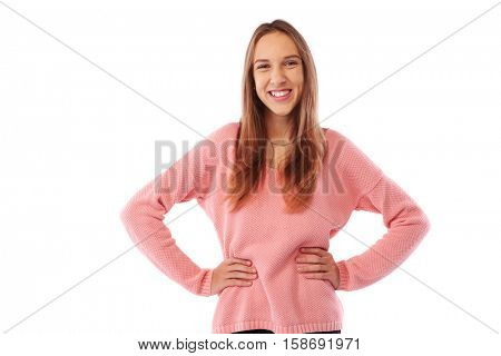 Mid shot of elated teenager standing in a confident pose with her hands on hips and smiling over white background