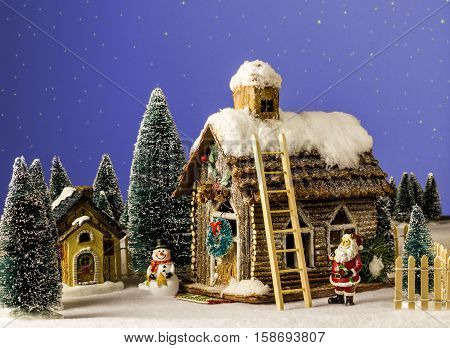 New Year Christmas house decorated with snow figure Santa Claus snowman next to wooden house.