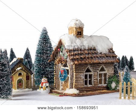 Isolated New Year Christmas house decorated with snow figure snowman next to wooden house.