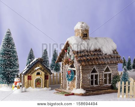 New Year Christmas house decorated with snow figure snowman next to wooden house.